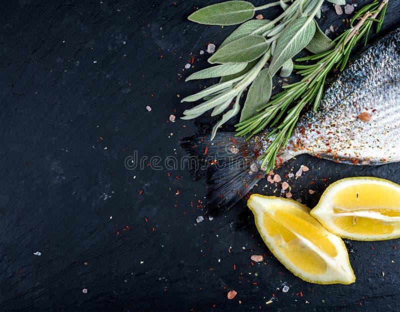 De staart van verse ruwe Dorado of de overzeese brasemvissen op zwarte leisteen schepen met kruiden, kruiden, citroen en zout in royalty-vrije stock afbeelding