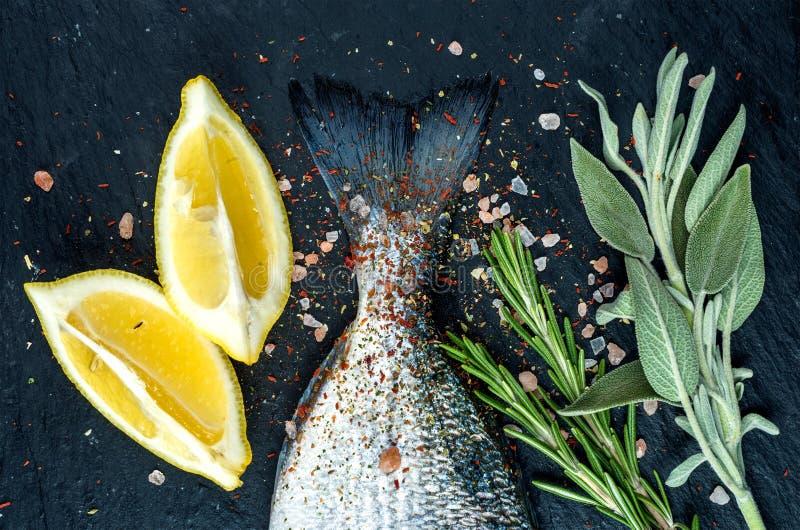 De staart van verse ruwe Dorado of de overzeese brasemvissen op zwarte leisteen schepen met kruiden, kruiden, citroen en zout in stock foto's