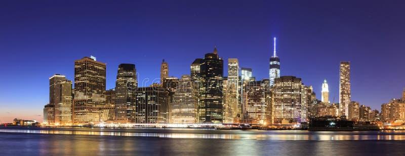 De Stad Manhattan van New York uit het stadscentrum bij schemer met wolkenkrabbersillumin stock foto's