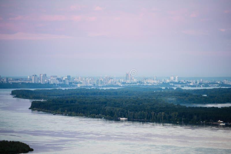 De stad over de rivier en het bos in de roze dageraad van de ochtendnevel royalty-vrije stock fotografie