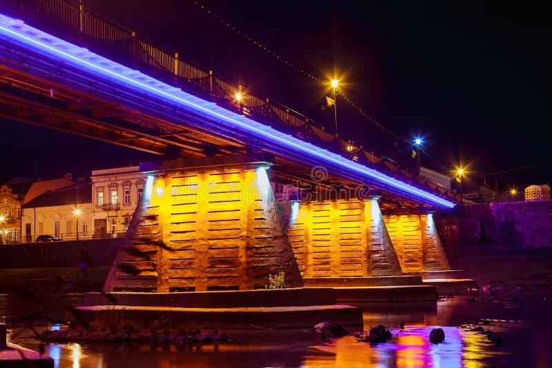 De stad van de brugnacht in water Uzhorod wordt weerspiegeld die stock afbeelding