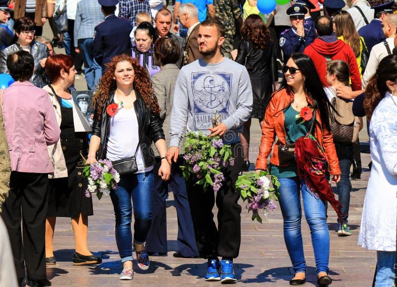 De stad van Dniepr, Dnepropetrovsk, de Oekraïne, 9 05 2018 De jongeren, een jongen en de meisjes gaat bloemen aan het Monument va stock afbeelding