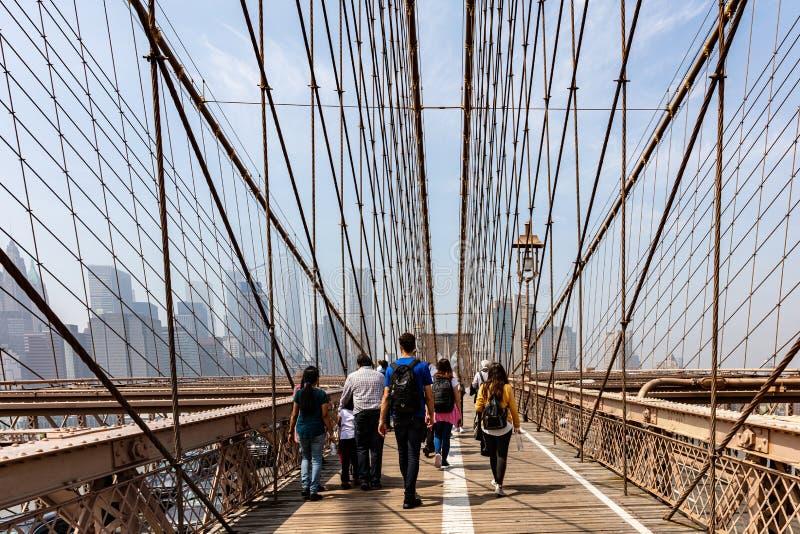 De stad van New York, de Mensen die van Manhattan op de Brug van Brooklyn, blauwe hemelachtergrond lopen stock afbeelding