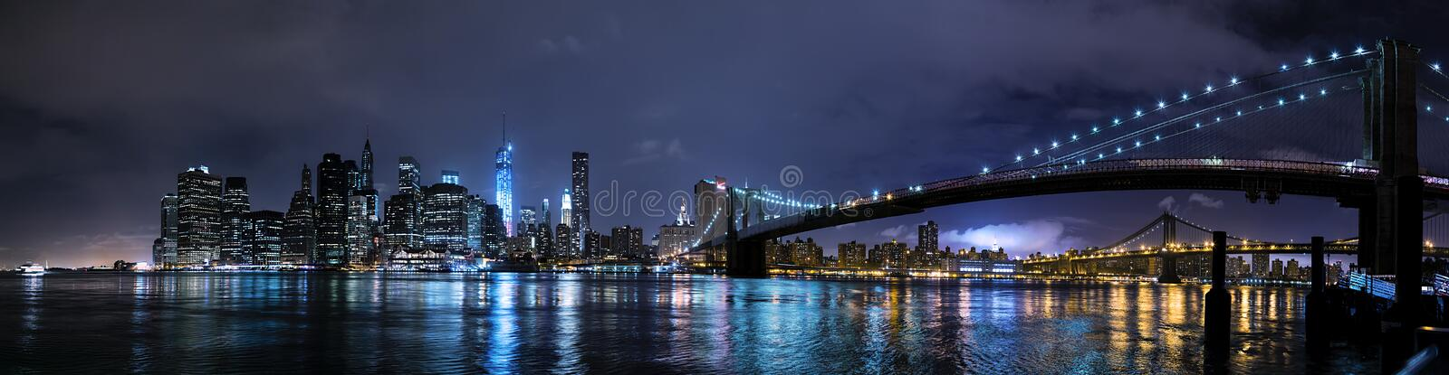 De Stad van New York, NY/USA - circa Juli 2015: Panorama van de Brug en 's nachts het Lower Manhattan van Brooklyn stock foto