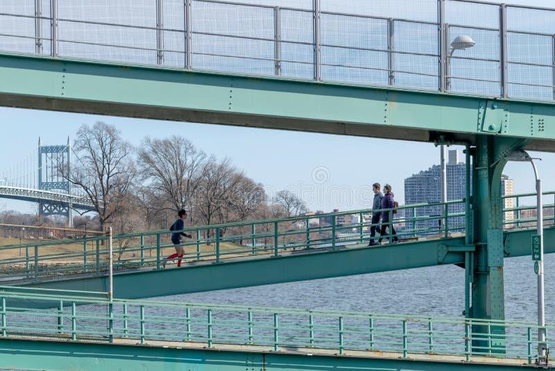 De Stad van New York, NY/USA - 3/19/2019: Mensen die een jogging langs een staalstructuur lopen naast de Rivier van het Oosten, m royalty-vrije stock foto
