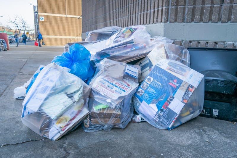 De Stad van New York, NY/USA - 03/19/2019: Recycling en vuilniszakken gevuld met document en karton op een de Stadsstraat van New royalty-vrije stock fotografie