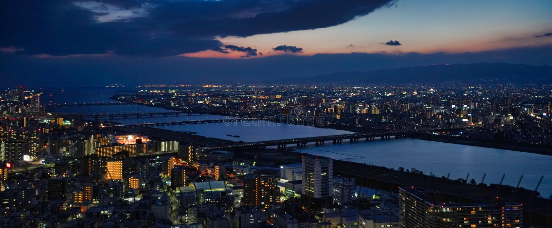 De stad van Osaka bij nacht stock afbeelding