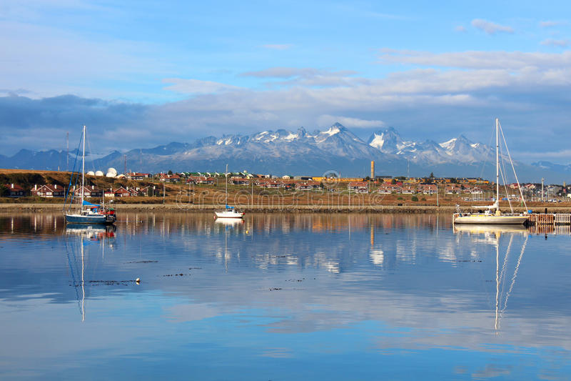 De stad van Ushuaia, de boten en de bergen op de achtergrond worden weerspiegeld in het water stock fotografie