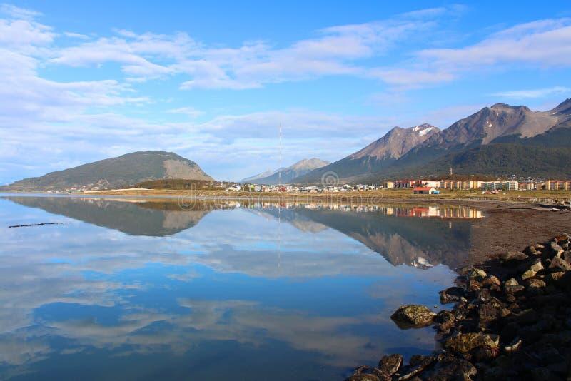 De stad van Ushuaia en de bergen op de achtergrond worden weerspiegeld in het water royalty-vrije stock fotografie