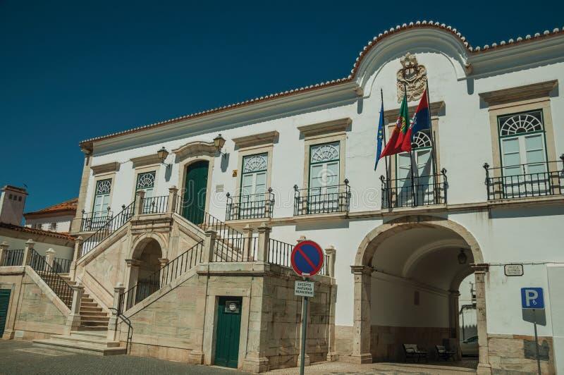 De stadhuisbouw met gang onder boog en vlaggen royalty-vrije stock afbeeldingen
