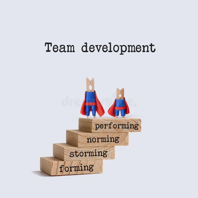 De stadia van de teamontwikkeling Het beeld van het groepswerkconcept met superherokarakters bovenop de houten trap woorden stock afbeelding