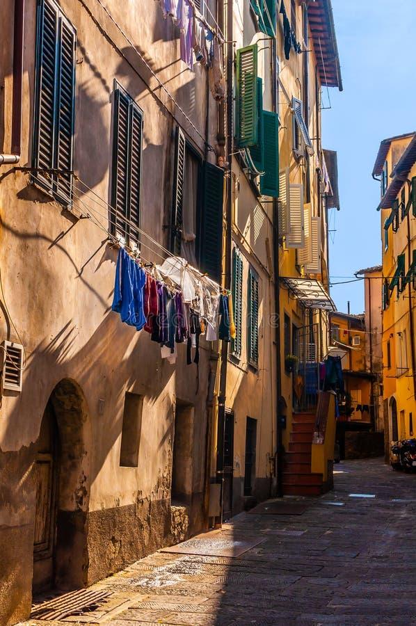 De stads kleine voetstraat van Italië gedeeltelijk in schaduwen met het drogen van kleren en lokale schaduwen royalty-vrije stock afbeeldingen