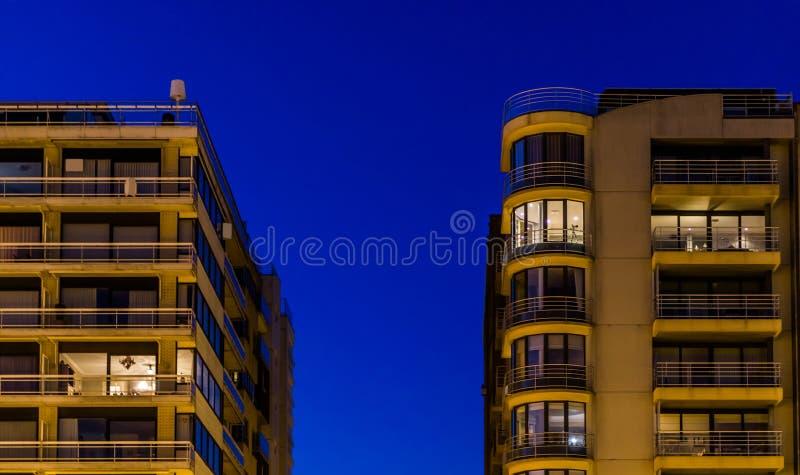 De stadsflats staken 's nachts aan, Architectuur in Blankenberge, België stock foto