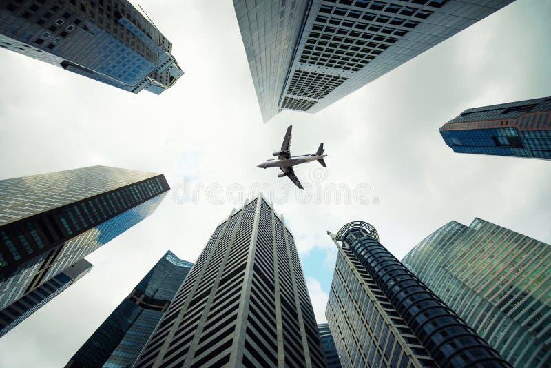 De stadsgebouwen van Singapore en een vliegtuig die boven in ochtend vliegen royalty-vrije stock foto
