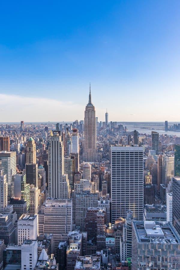 De Stadshorizon van New York in Manhattan de stad in met Empire State Building en wolkenkrabbers op zonnige dag met duidelijke bl stock afbeeldingen