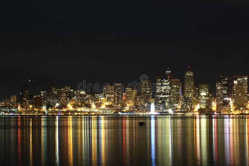 De stadshorizon van Seattle bij nacht met lichten in water worden weerspiegeld dat stock afbeeldingen