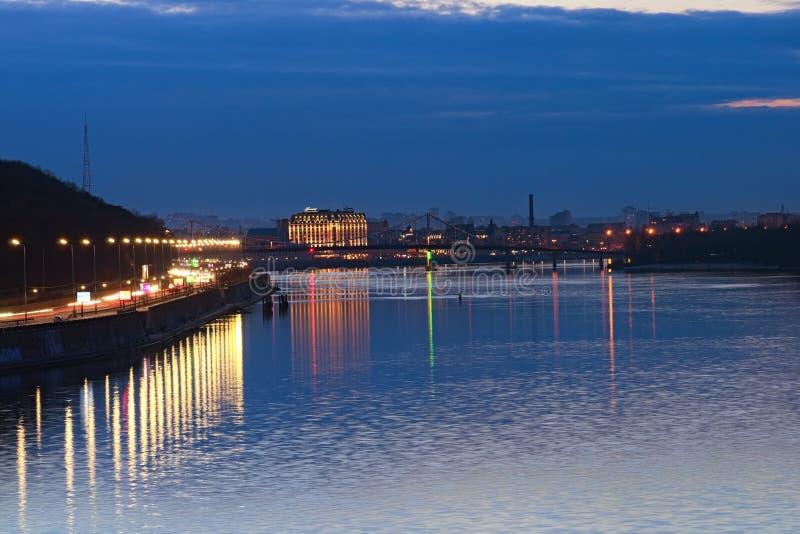 De stadslandschap van de nacht Verlichte Voetbrug over Dnipro-Rivier, silhouetten van gebouwen binnen royalty-vrije stock afbeelding