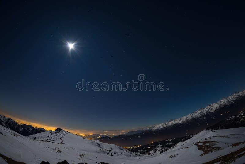 De stadslichten van Turijn, nachtmening van sneeuw behandelde Alpen door maanlicht Maan en Orion-constellatie, duidelijke hemel,  stock fotografie