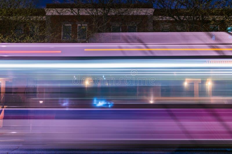 De Stadsopenbaar vervoer van New York, MTA die buss onderaan een nachtstraat swooshing in Harlem, NYC, de V.S. stock afbeeldingen