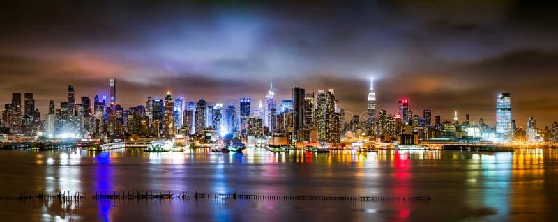 De Stadspanorama van New York op een bewolkte nacht stock foto
