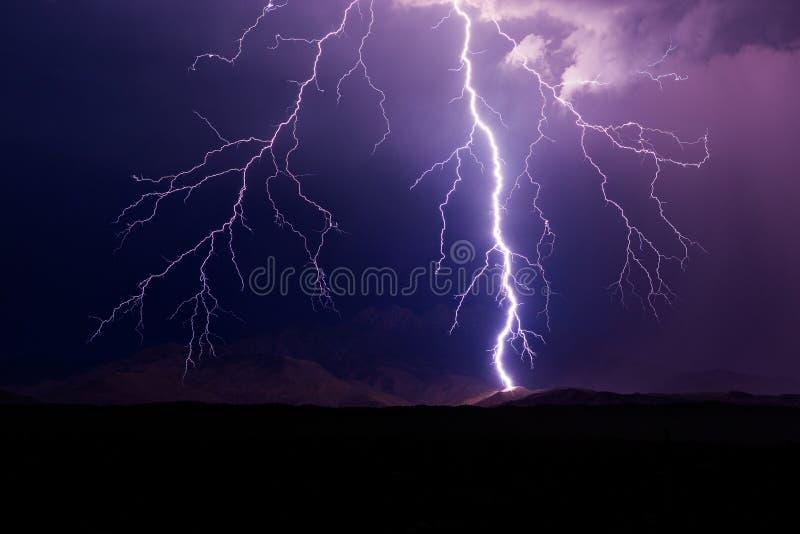 De staking van de bliksembout tijdens een onweer met bergen op de achtergrond royalty-vrije stock foto's