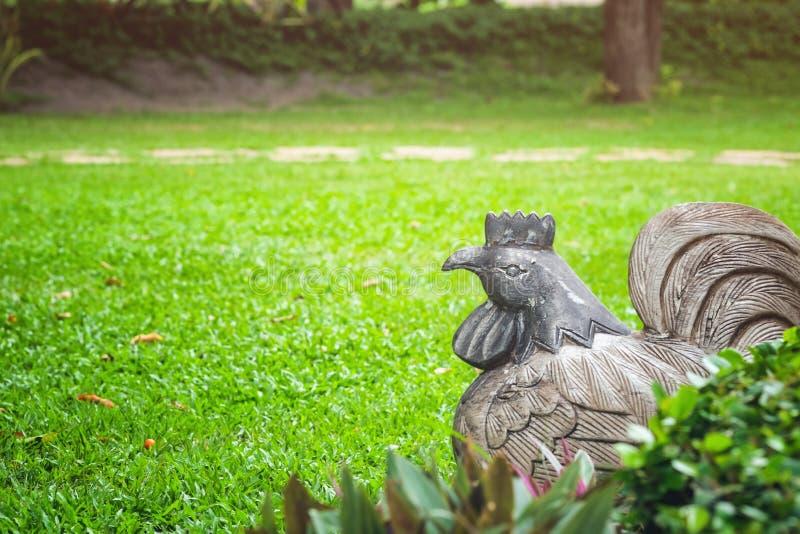 De standbeelden, kippen zijn op het gras en de groene bomen stock foto