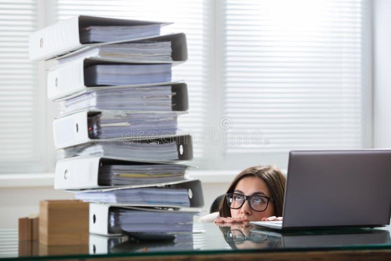 De Stapel van onderneemsterpeering the folders in Bureau stock foto's
