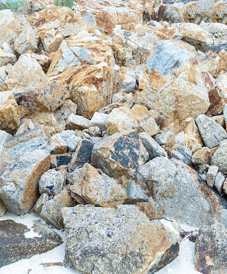 De stapel van stenen doorstond beige deel van het strand natuurlijke achtergrond overzeese als achtergrond kustwild stock afbeelding