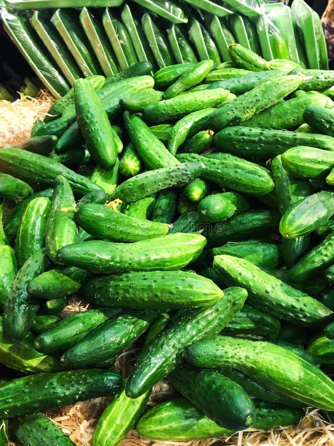 De stapel van verse organische groene komkommers op een markt sluit omhoog stock afbeelding