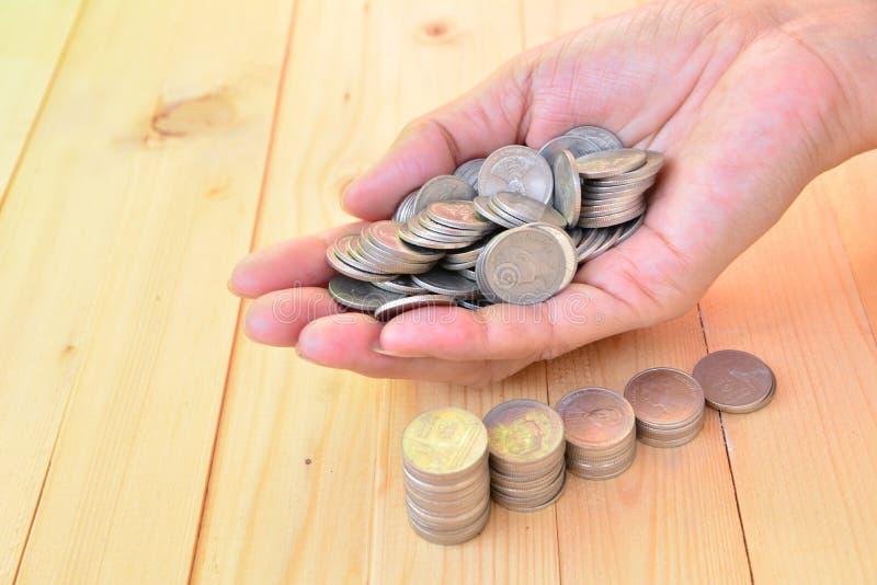 De stapelmuntstukken zetten op hand voor sparen geld en financieel, belastingsseizoen stock fotografie