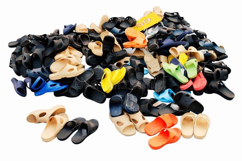 De stapels van schoenen verkochten in diverse kleurencombinaties landelijke landmarkt, sandals, toevallige oude schoenen, Op witt stock fotografie