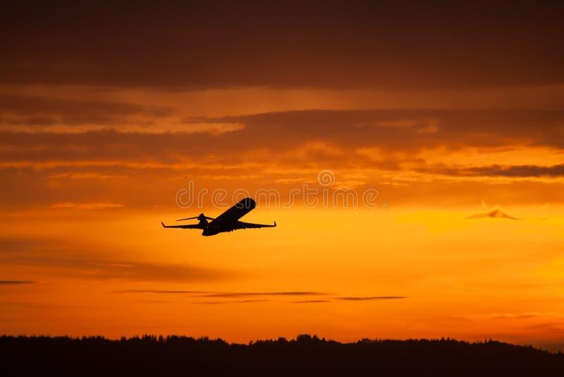 De start van het vliegtuig in zonsondergang stock afbeelding