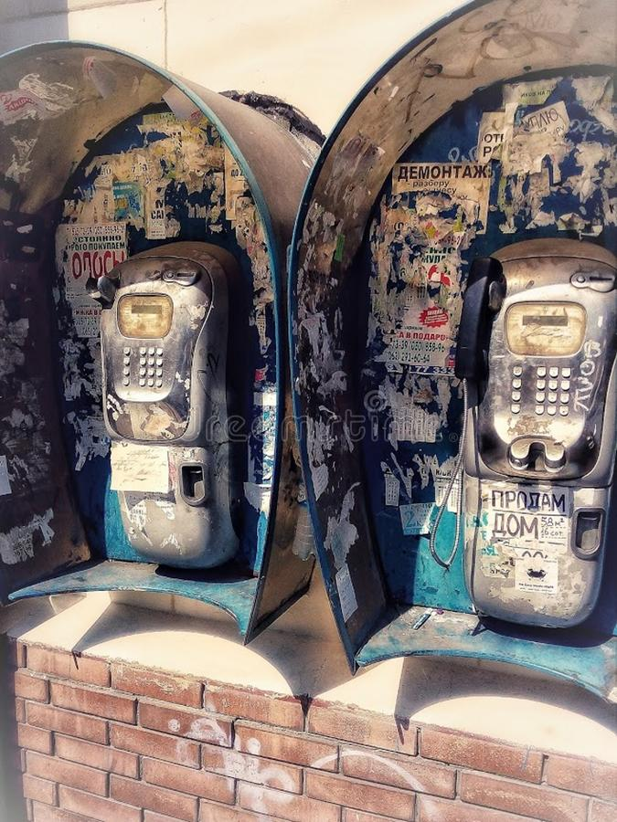 de 20ste eeuwpublieke telefooncellen op een stadsstraat, oude advertenties op een muur, telefoons met ontvangers stock foto