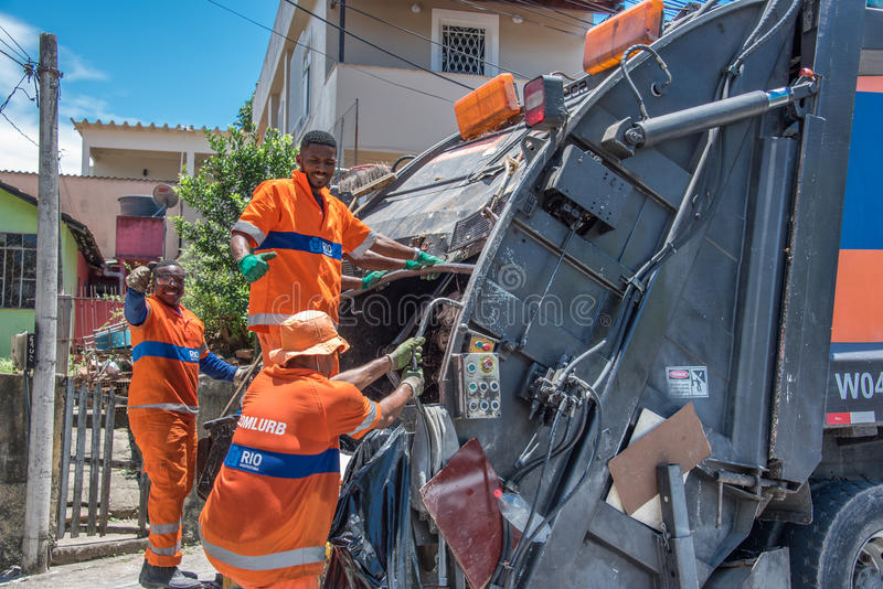 De stedelijke arbeiders van gemeentelijke COMLURB die afval zetten in het recycling van vuilnisauto stock foto's