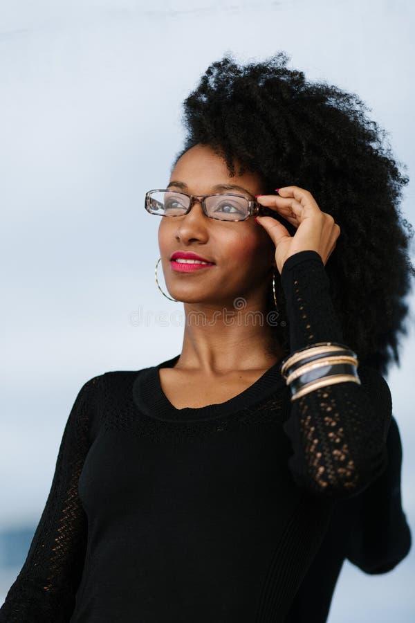De stedelijke onderneemster van het afrokapsel buiten het dragen van glazen stock foto
