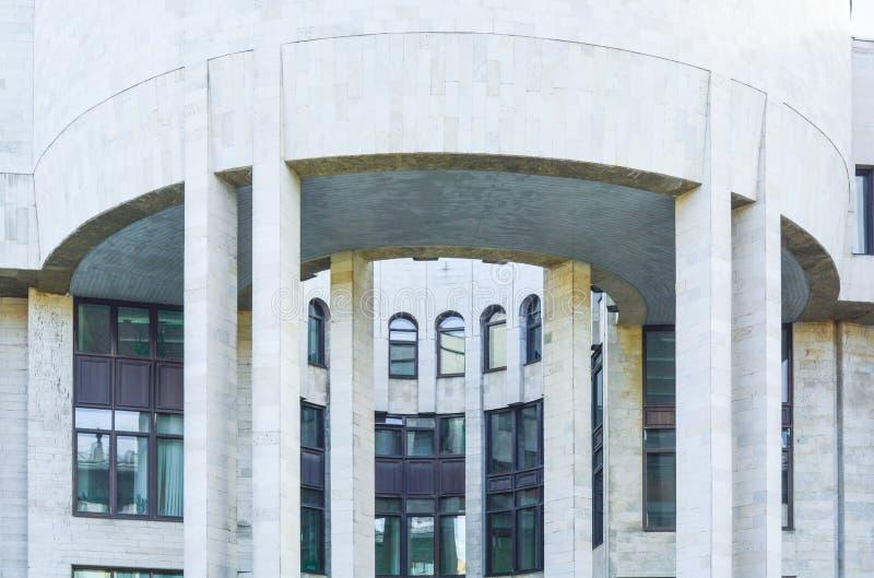 De stedelijke stads moderne bouw met halfronde richel met kolommen Oud rijtjeshuis stock foto