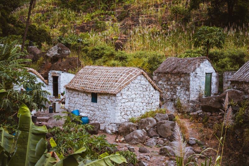 De steenhuizen in lokale stijl met stro behandelden daken en blauwe vensters tussen weelderige groene vegetatie en berg stock afbeelding