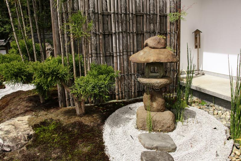 De steenlantaarn en de bamboeverdeling in traditionele Japanse zen tuinieren in Hasedera, Kamakura, Japan stock foto's