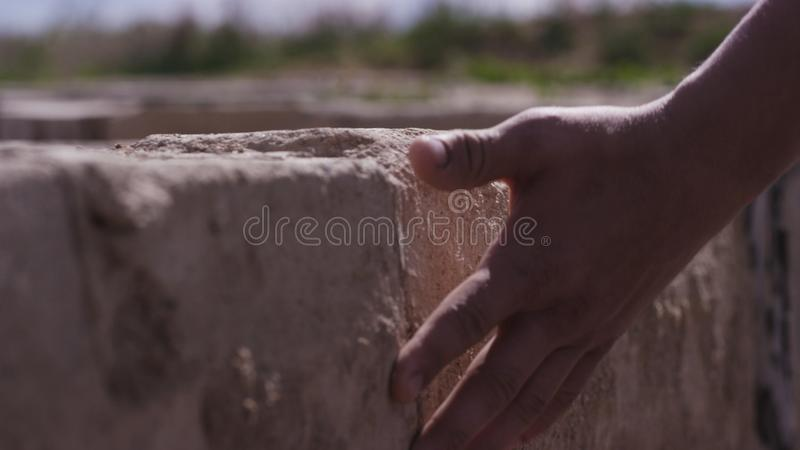 De steenmuur van de handaanraking De hand bemant aanrakingen de steenmuur Mens die naar het inheemse land en de plaatsen, het con royalty-vrije stock afbeelding