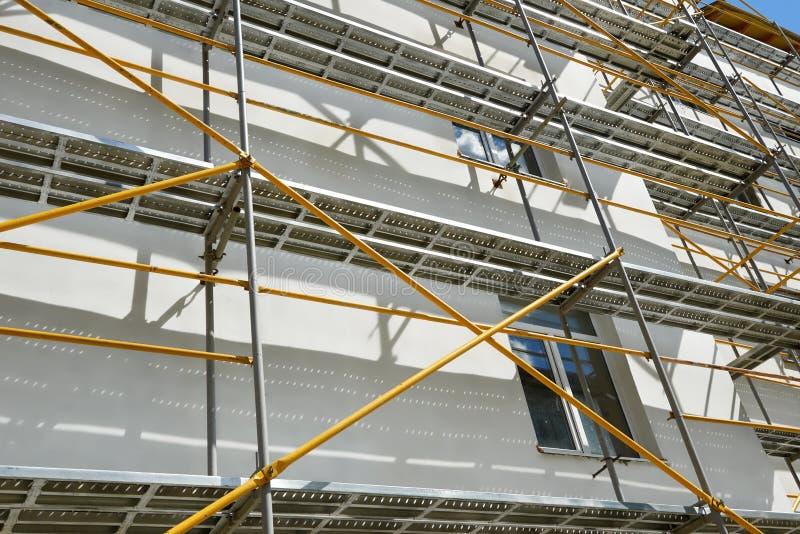 De steiger dichtbij een huis in aanbouw voor extern pleister werkt, hoog flatgebouw in stad, wit muur en venster, ye royalty-vrije stock foto