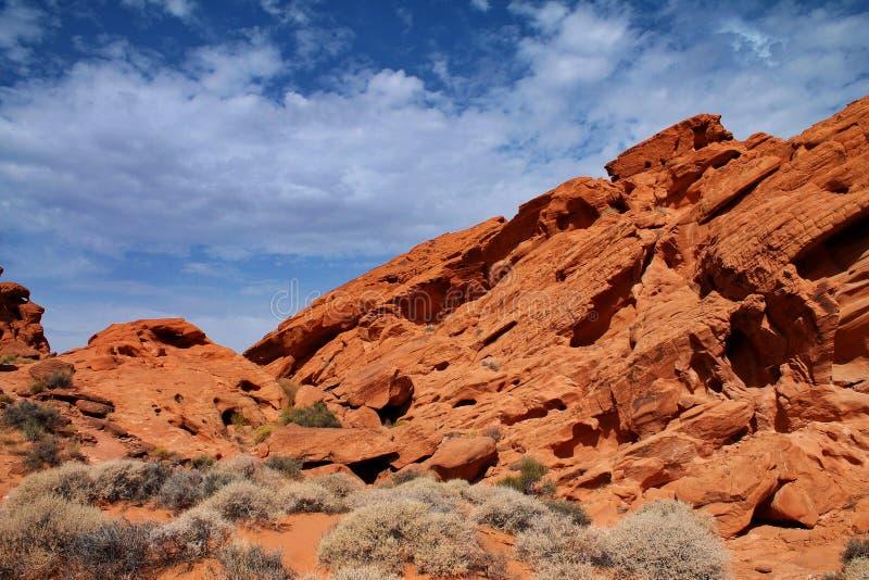 De steile oranje boven de zandige vloer toenemen en kleine rotsen die schrobben struiken in Nevada royalty-vrije stock fotografie