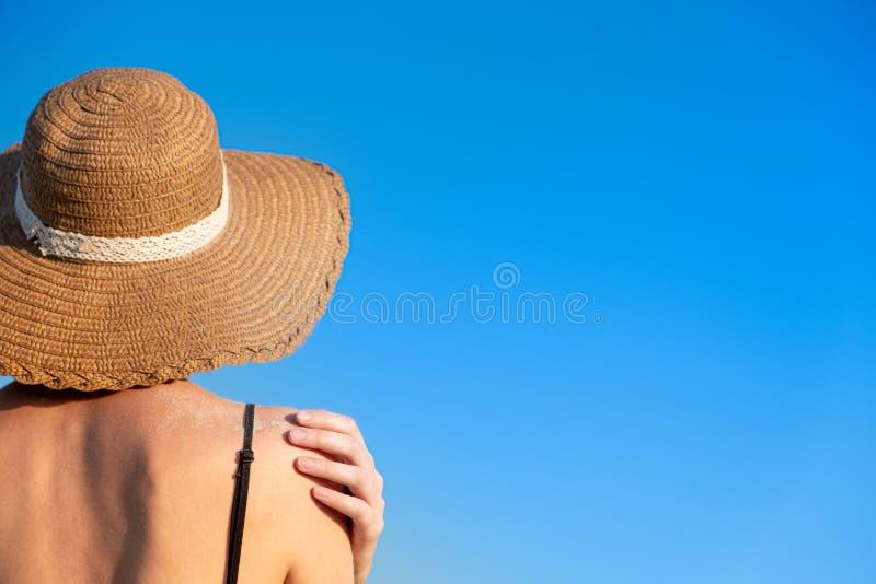 De stemming van de de zomervakantie: wijfje in strandhoed, die in zand op heldere blauwe achtergrond wordt behandeld royalty-vrije stock fotografie