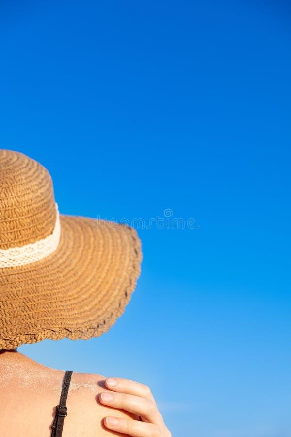 De stemming van de de zomervakantie: wijfje in strandhoed, in zand op heldere blauwe achtergrond wordt behandeld die stock foto