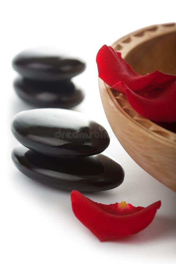De stenen en de bloemblaadjes van Zen in geïsoleerde kom royalty-vrije stock afbeeldingen