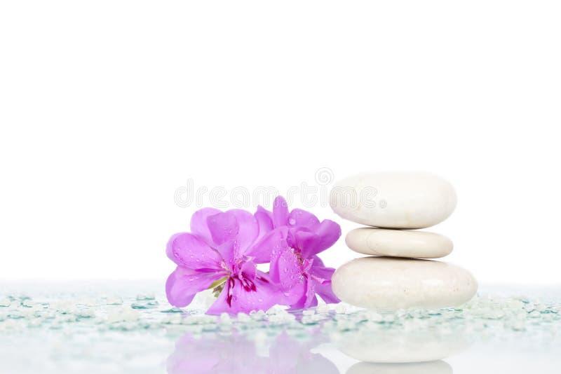 De stenen van het kuuroord en roze bloem stock foto