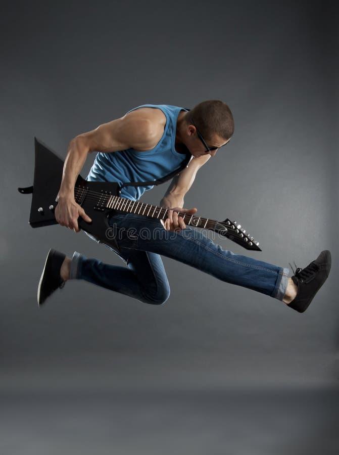 De ster die van de rots met gitaar springt royalty-vrije stock fotografie