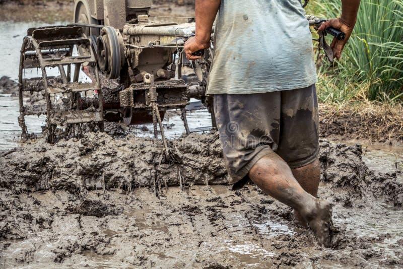 De sterke Aziatische tractor van de landbouwers drijfuitloper op modderig gebied, detail van het mannelijke landbouwer lopen bloo stock foto's