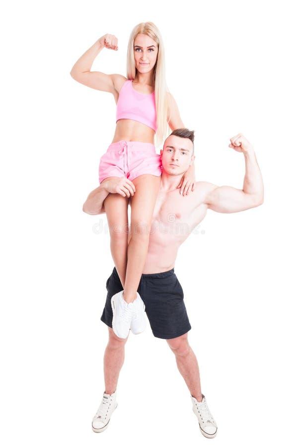 De sterke bodybuilderman vrouw van de holdingsgeschiktheid op zijn schouder royalty-vrije stock fotografie