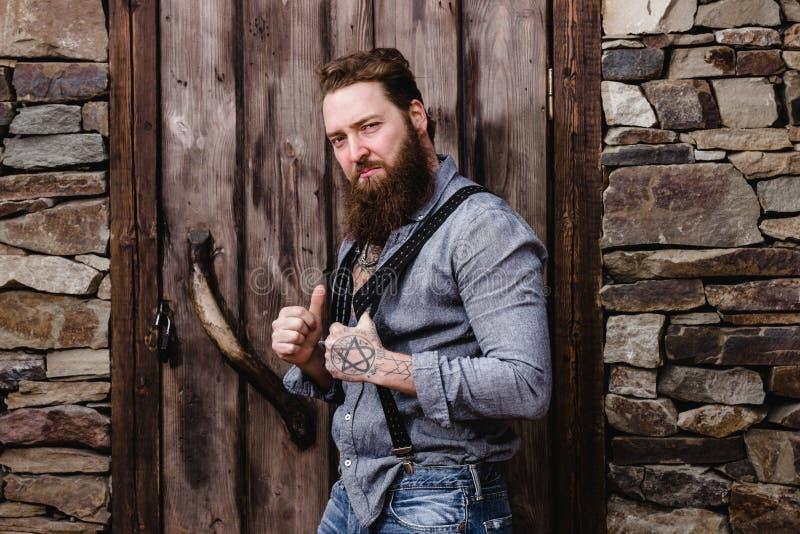 De sterke brutale mens met een baard en tatoegeringen op zijn handen gekleed in modieuze vrijetijdskleding stelt op de achtergron stock afbeeldingen