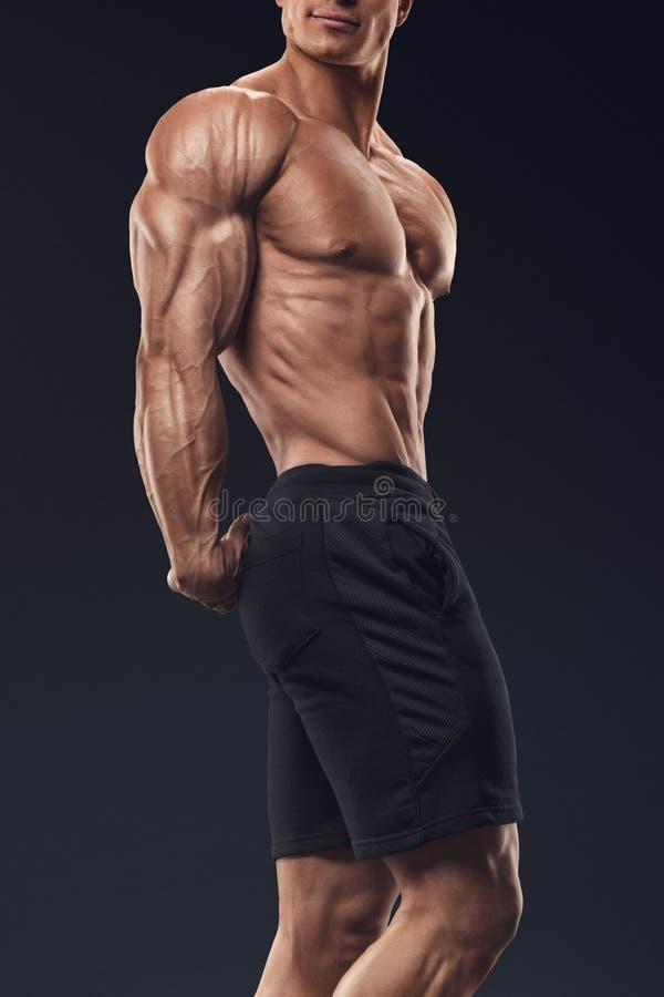 De sterke en knappe jonge bodybuilder toont zijn spiert aan stock afbeeldingen
